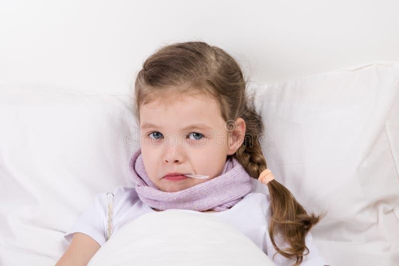 Маленькая девочка с перевязанной болью в горле лежит в кровати и держит термометр для того чтобы измерить температуру в ее рте стоковое изображение rf