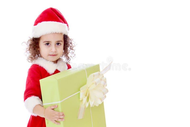 Маленькая девочка с подарком в шляпе Санта Клауса стоковые фотографии rf