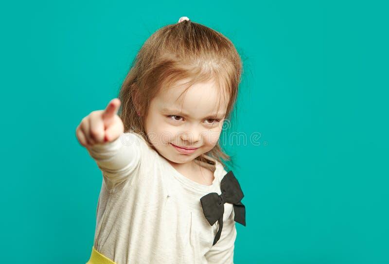 Маленькая девочка с рассерженной стороной указывает ее палец на камеру, обвиняет вас что-то, жалуется, показывается тайну стоковые фотографии rf