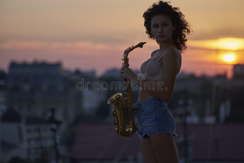 Маленькая девочка с саксофоном на крыше стоковое изображение