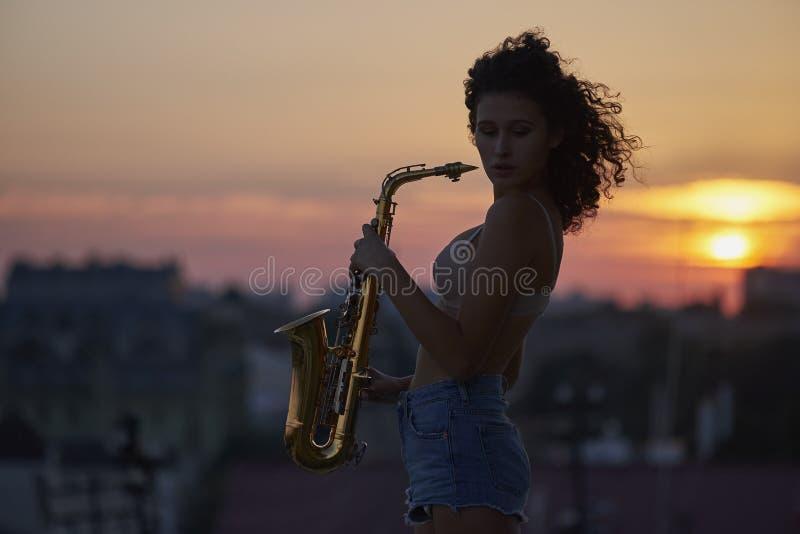 Маленькая девочка с саксофоном на крыше стоковые изображения rf