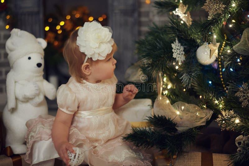Маленькая девочка с удивленным взглядом на горении освещает на рождественской елке стоковые фото