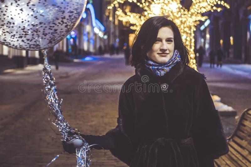 Маленькая девочка с baloon идя в улицы города ночи стоковое изображение