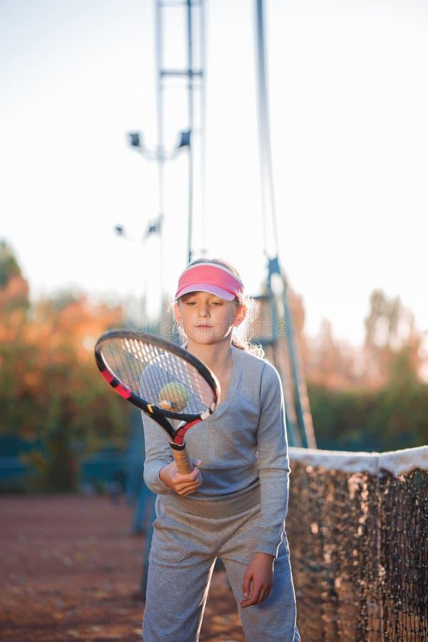 Маленькая девочка, теннисист, активно играть, бросая шарик на ракетке тенниса стоковое фото rf