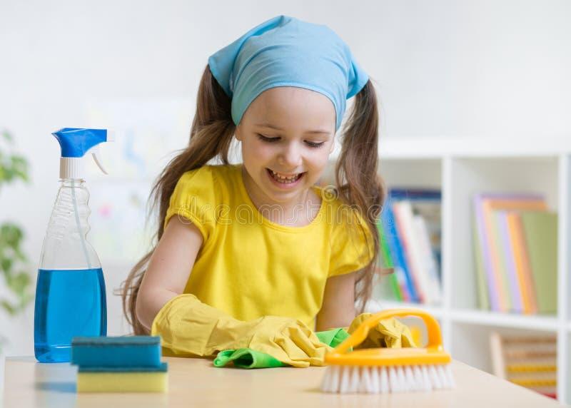Маленькая девочка убирая ее комната Оягнитесь обтирать таблицу с бульварной газетенкой и владения распыляют на таблице стоковое фото rf