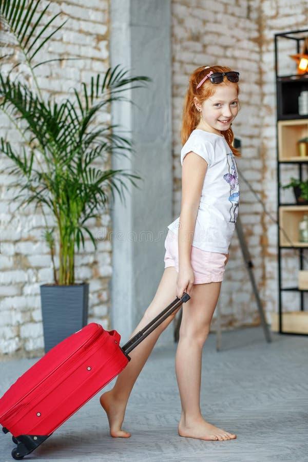 Маленькая девочка упаковала вещи в чемодане на каникулах Концепция, стоковые изображения rf
