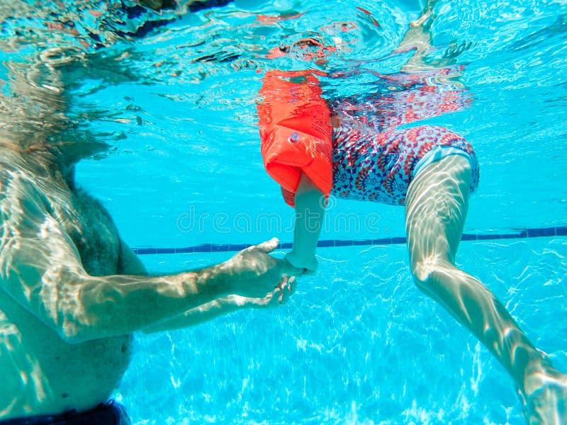 Маленькая девочка уча поплавать под водой стоковые фото