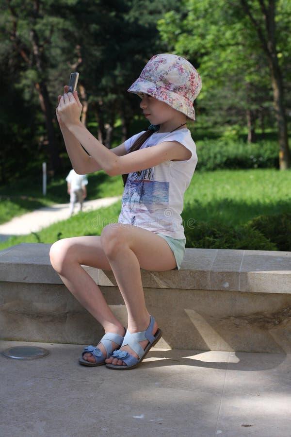 Маленькая девочка фотографирует с камерой мобильного телефона в природе, в горах стоковое фото