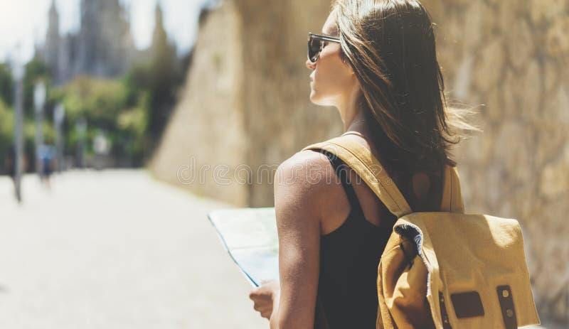 Маленькая девочка хипстера с солнечными очками и ярким рюкзаком использующ и смотрящ карту Путешественник сказанного взгляда тури стоковые фотографии rf