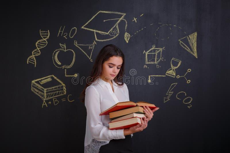 Маленькая девочка читая стог различных книг, стоя рядом с whiteboard стоковое фото rf