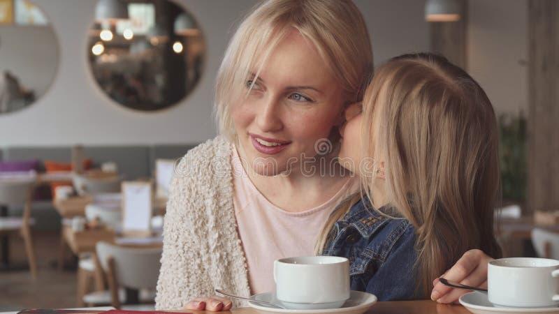 Маленькая девочка шепчет в ее ухе ` s матери на кафе стоковое фото