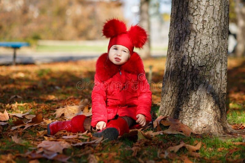 Маленькая девочка штыря-вверх тележки toothsome нося красную blushful куртку зимы и теплая шляпа с ботинками фасонируют стильные  стоковые фото