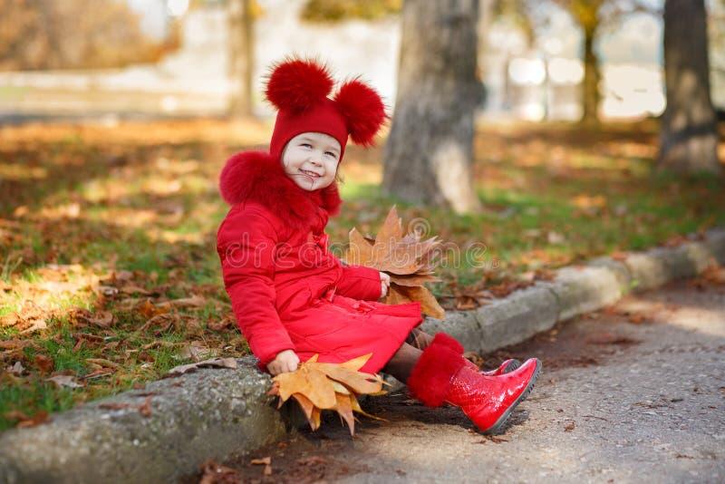 Маленькая девочка штыря-вверх тележки toothsome нося красную blushful куртку зимы и теплая шляпа с ботинками фасонируют стильные  стоковые изображения rf