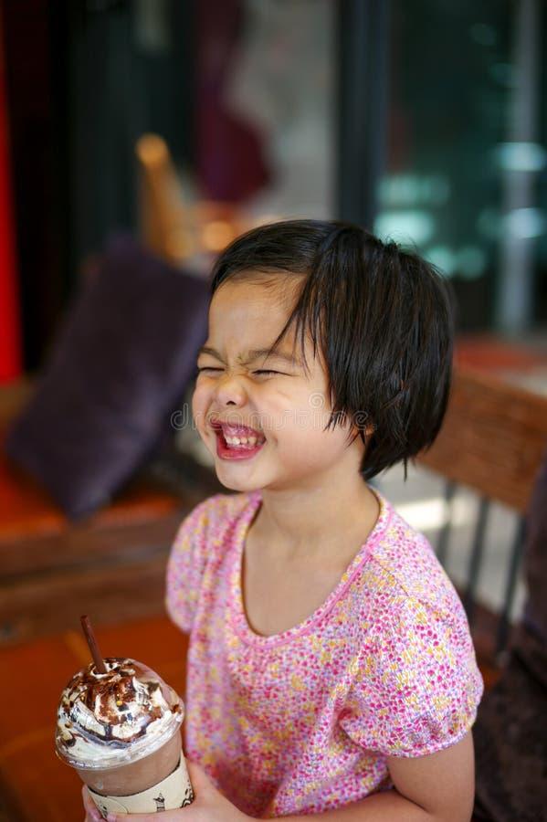 Маленькая девочка Portriat азиатская выпивая смешанный шоколад льда со смешной стороной Счастливая девушка наслаждается съесть бе стоковые фото