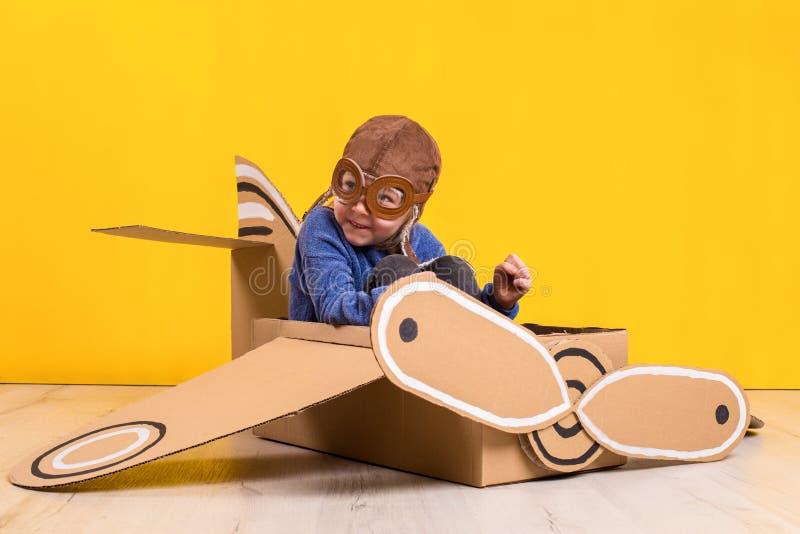 Маленькая девушка фантазера играя с самолетом картона Детство Фантазия, воображение стоковое изображение rf