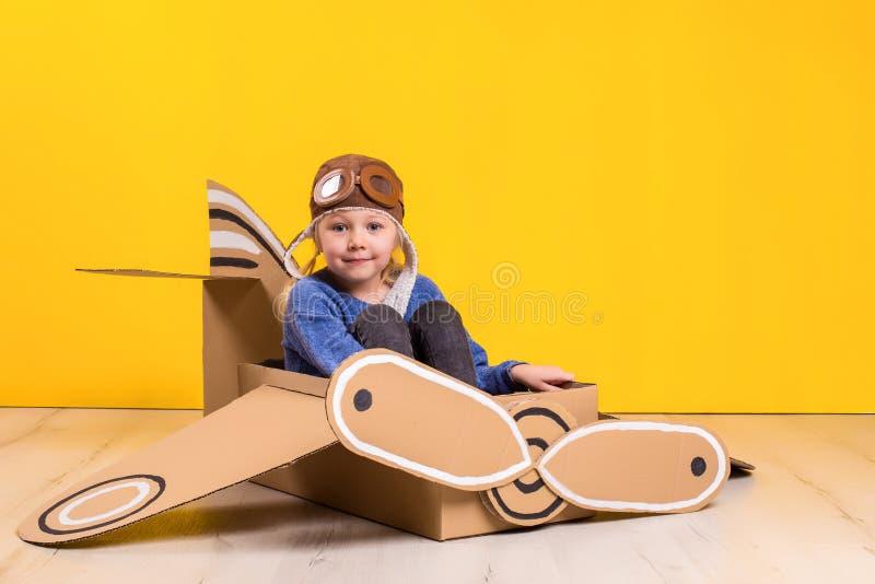 Маленькая девушка фантазера играя с самолетом картона Детство Фантазия, воображение стоковые фото