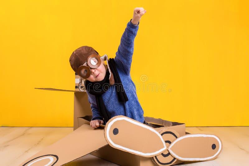 Маленькая девушка фантазера играя с самолетом картона Детство Фантазия, воображение стоковая фотография rf