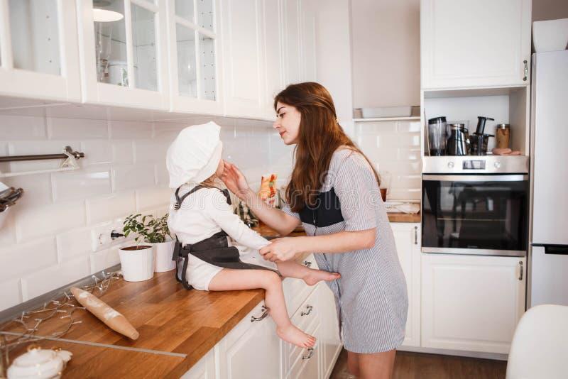 Маленькая дочь в шляпе и рисберме шеф-повара и ее мать подготавливают выпечку в яркой, классической кухне стоковое фото