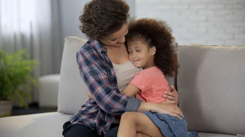 Маленькая дочь плотно snuggling к любимой матери, полному доверию и привязанности стоковые изображения rf