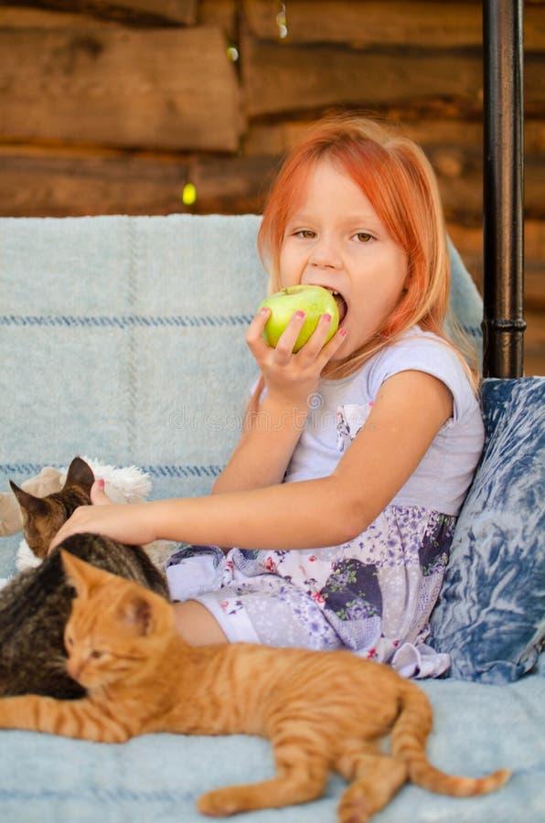 Маленькая кавказская девушка 6 лет сидит на качании сада, играет с котятами и ест зеленые яблоки t стоковые изображения rf