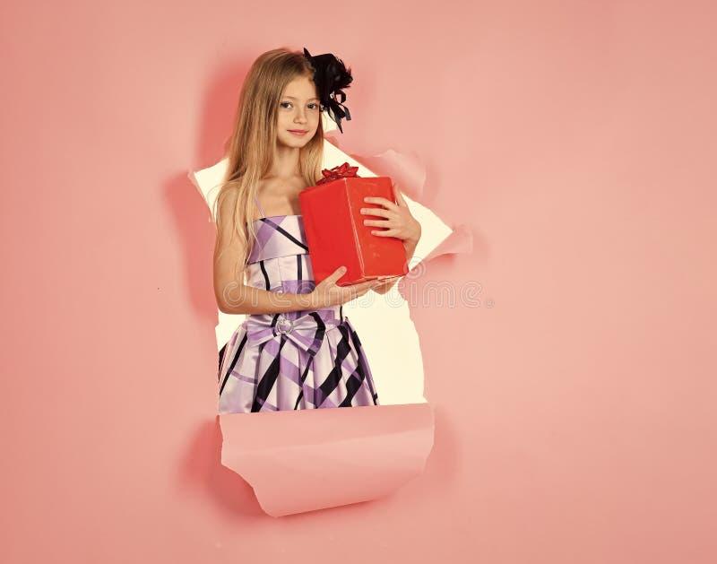 Маленькая кавказская улыбка девушки и держать красную подарочную коробку на розовой предпосылке Ребенок держа коробку подарка Сча стоковая фотография rf