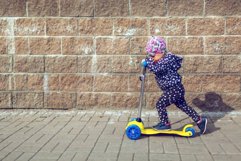 Маленькая красавица с соской катается на детской скутере на улице Концепция деятельности детей и стоковые фото