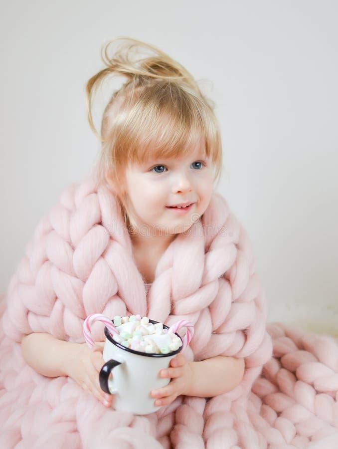 Маленькая красивая кавказская девушка держа чашку с рождеством горячего шоколада ждать и Новым Годом, одеялом пастельным Pi Merin стоковые фото