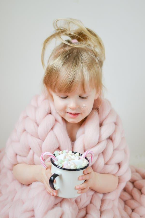 Маленькая красивая кавказская девушка держа чашку с рождеством горячего шоколада ждать и Новым Годом, одеялом пастельным Pi Merin стоковая фотография rf