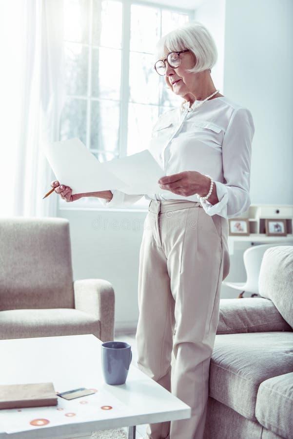 Маленькая красивая пенсионерка в бежевых брюках, занимающаяся семейны стоковое фото