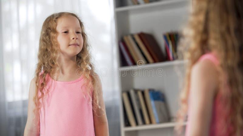 Маленькая курчавая девушка coquetting перед зеркалом, мечтая для того чтобы стать взрослый, ребенок стоковая фотография rf