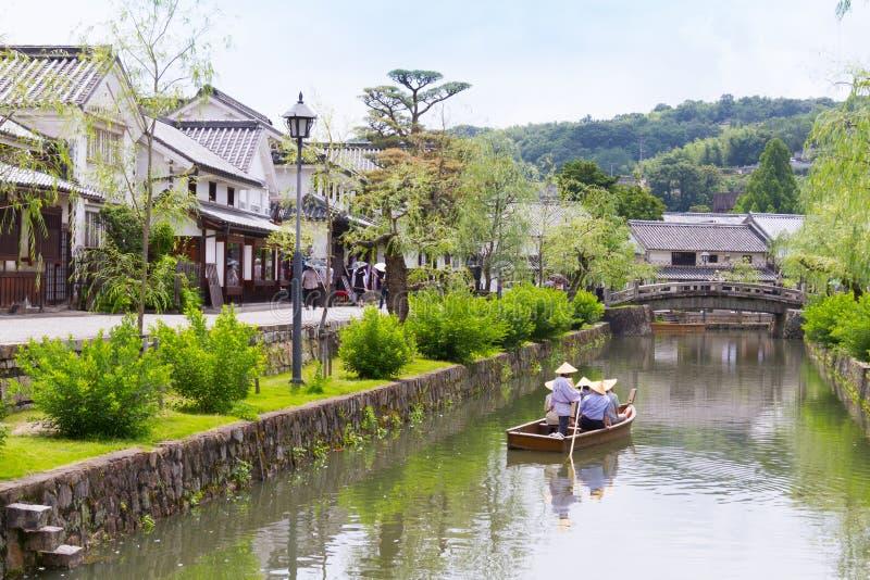 Маленькая лодка идя на канал в Kurashiki, Японии стоковое изображение
