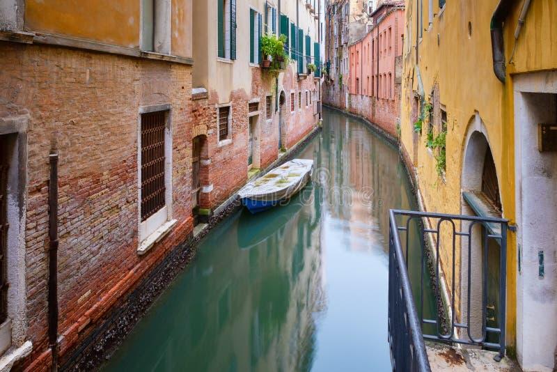 Маленькая лодка на узком канале окруженном старыми выдержанными зданиями в Венеции стоковое фото