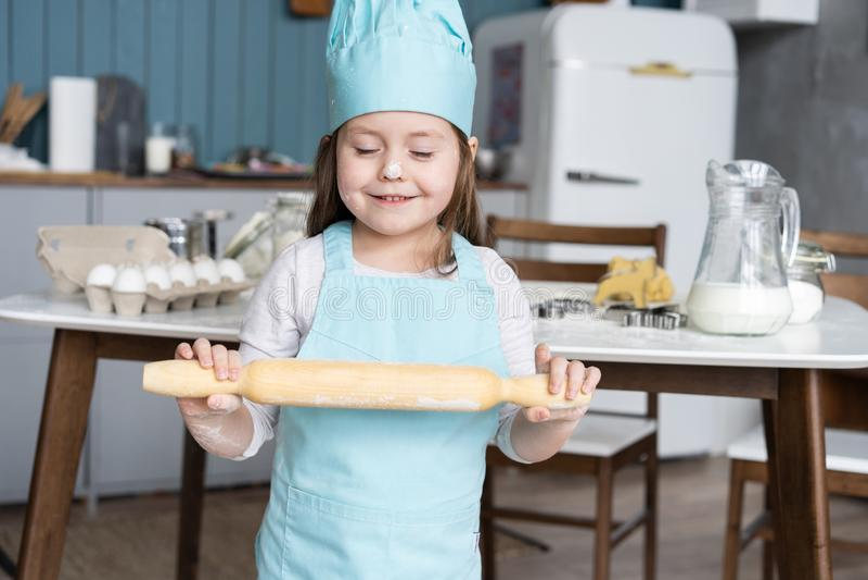 Маленькая милая девушка варит на кухне Иметь потеху пока делающ торты и печенья Усмедущся и смотрящ камеру стоковые фото