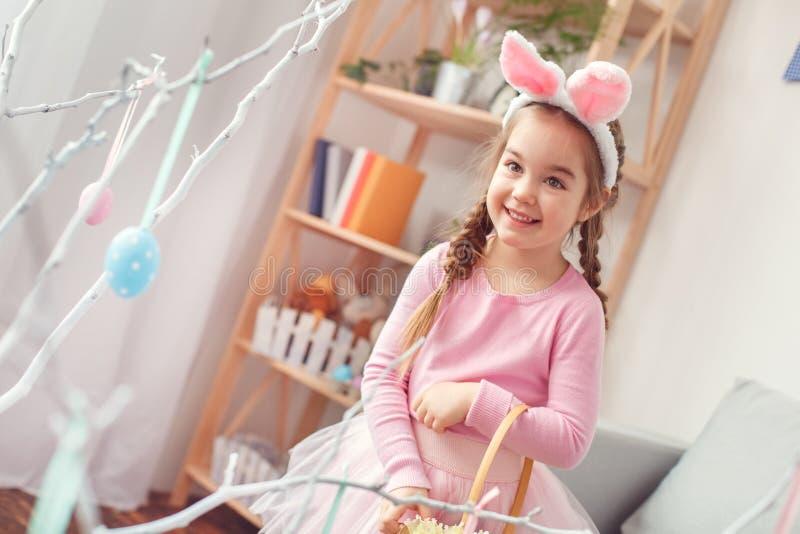 Маленькая милая девушка в концепции торжества пасхи ушей и платья зайчика дома смотря яичко на возбужденной ветви стоковая фотография rf