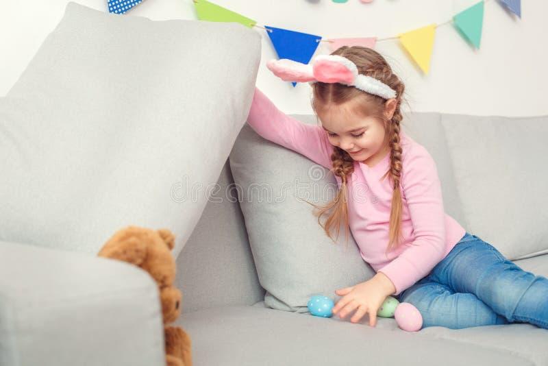 Маленькая милая девушка в яичках концепции торжества пасхи ушей зайчика дома пряча под подушкой стоковые фото