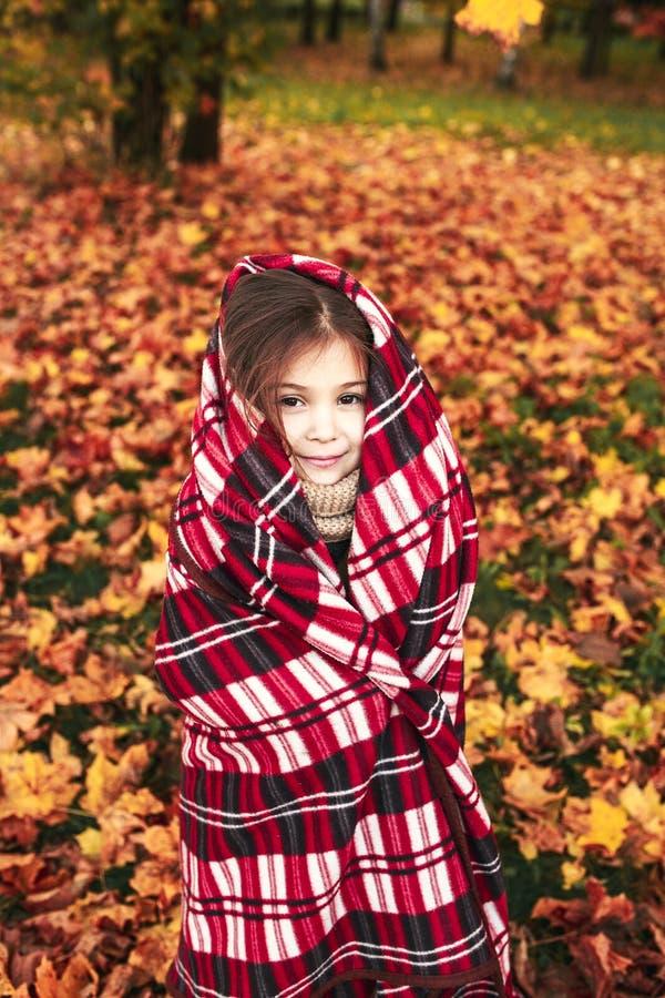 Маленькая милая девушка играет в листьях осени в парке стоковые изображения