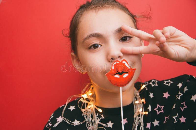 Маленькая милая девушка подпирает губы и гирлянду на красной предпосылке стоковое изображение