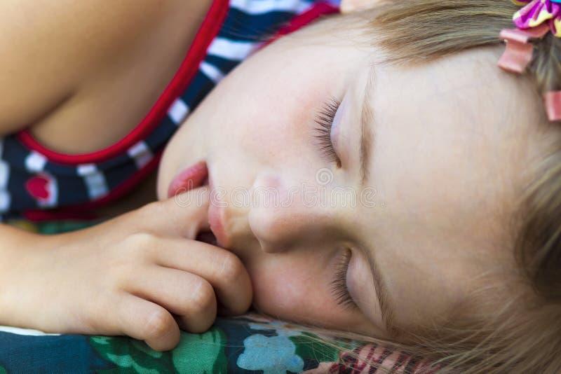 Маленькая милая девушка спать, всасывая большой палец руки и имея сладостное drea стоковое фото
