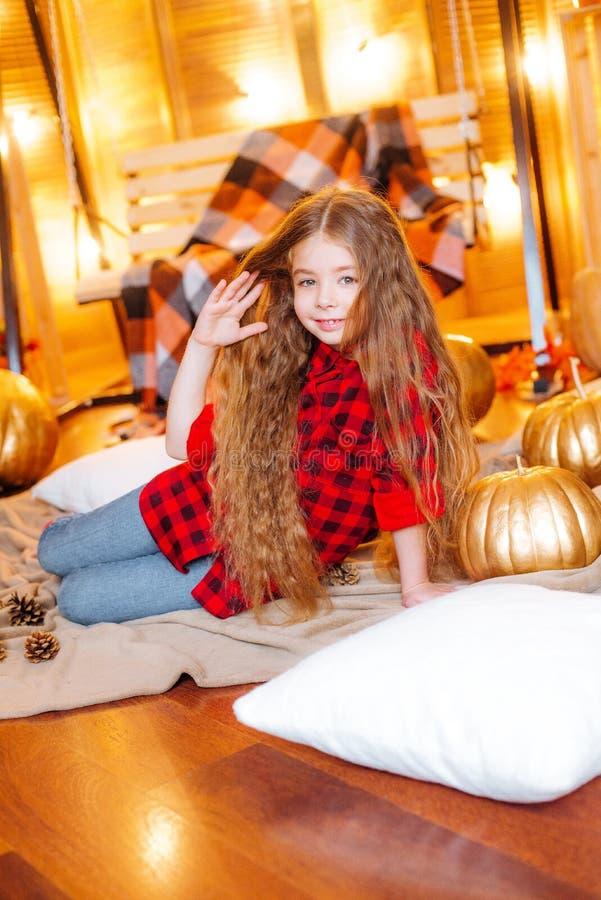 Маленькая милая девушка с длинным вьющиеся волосы около качания и тыквами в красном цвете в красной checkered рубашке стоковая фотография