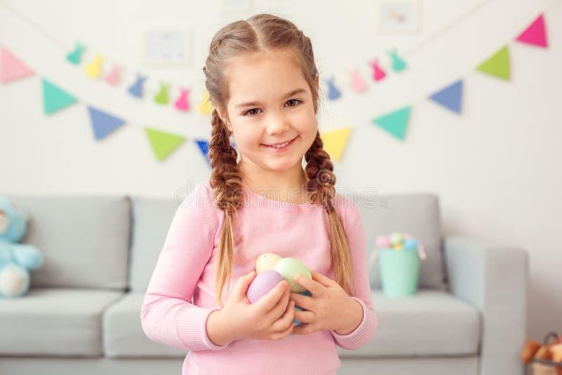 Маленькая милая концепция торжества пасхи девушки дома стоя держащ eggs смотреть конец-вверх камеры стоковое фото rf