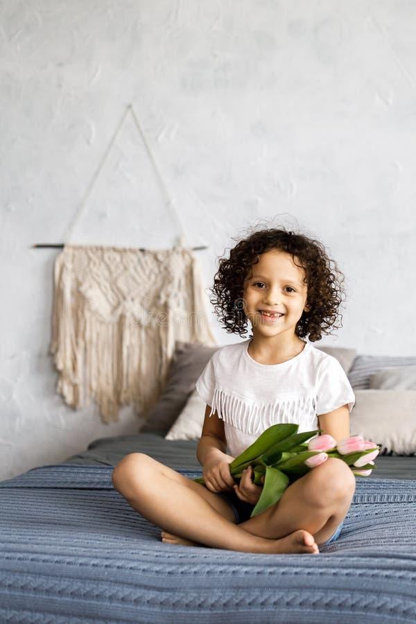 Маленькая милая курчавая девушка сидя на ее кровати с тюльпанами в ее оружиях стоковые фотографии rf