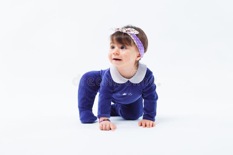Маленькая милая любознательная прелестная усмехаясь девушка с смычком в сидеть волос вползая в студии представляя на белой предпо стоковое изображение