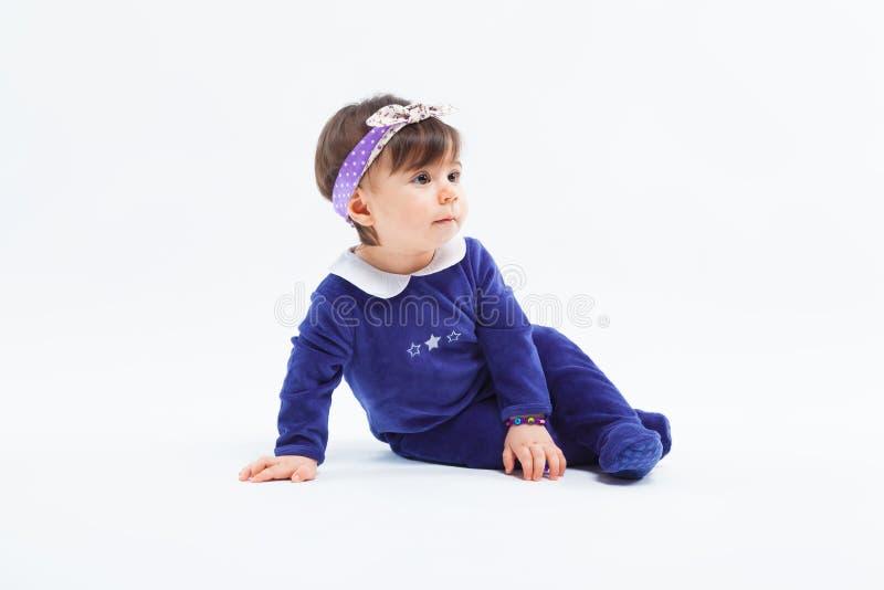 Маленькая милая прелестная девушка с смычком в волосах сидя в студии представляя на белой предпосылке стоковое фото
