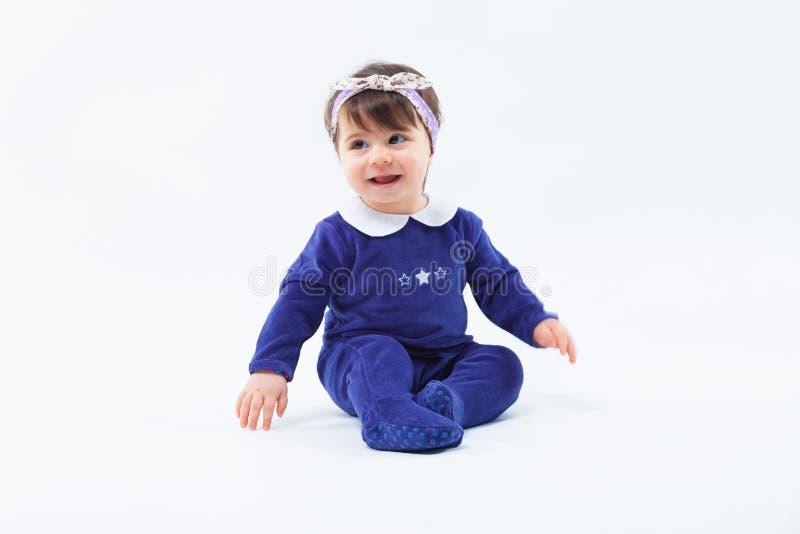 Маленькая милая прелестная усмехаясь девушка с смычком в волосах сидя в студии представляя на белой предпосылке стоковая фотография rf