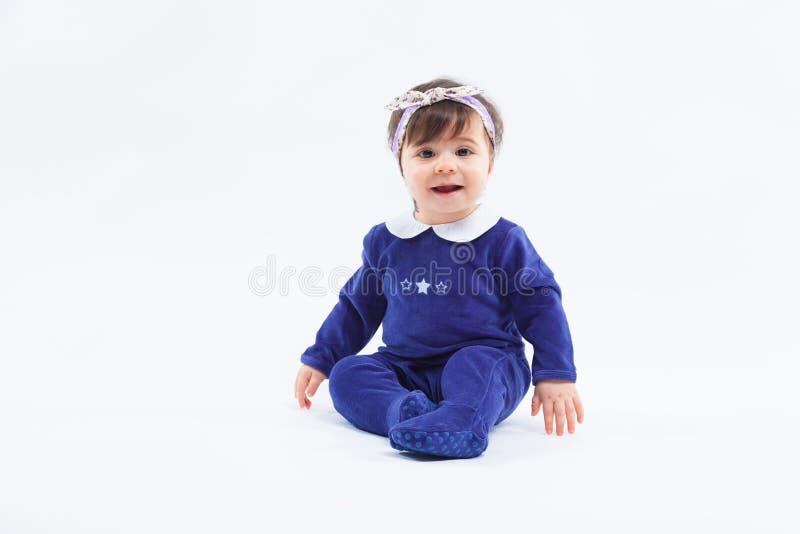 Маленькая милая прелестная усмехаясь девушка с смычком в волосах сидя в студии представляя на белой предпосылке стоковое фото