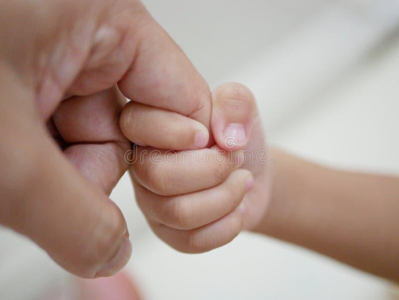 Маленькая рука младенца держа палец ` s отца представляя влюбленность, интимность, и помощь отц-и-ребенка стоковое фото