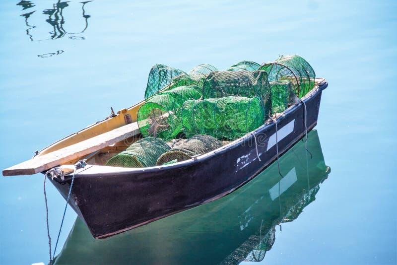Маленькая сиротливая шлюпка рыб с сетями стоковое фото