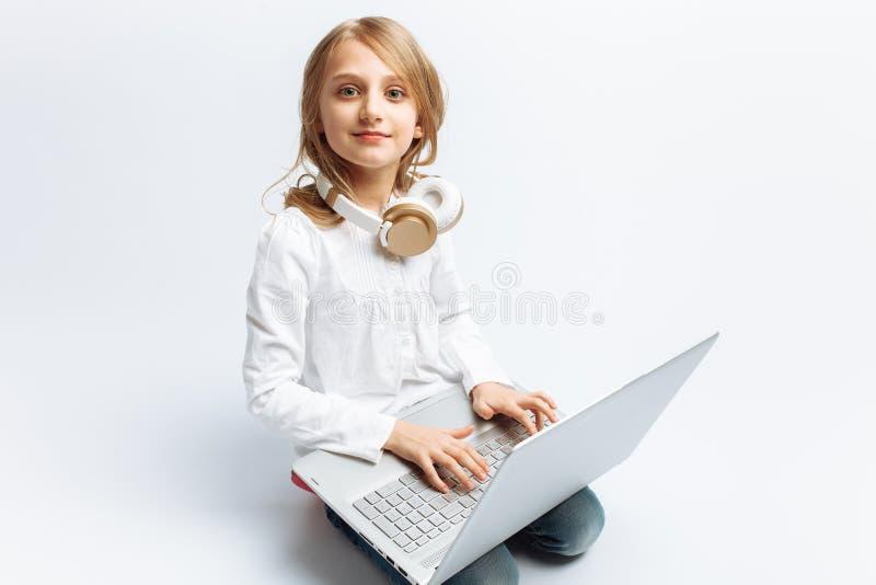 Маленькая современная девушка сидя с компьтер-книжкой и слушая к музыке, на изолированной предпосылке, милый и красивый стоковые изображения rf