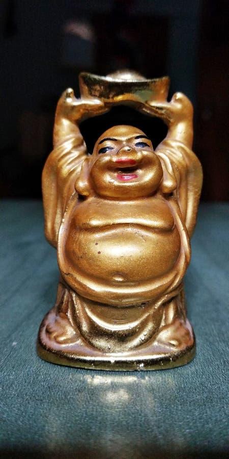 Маленькая статуя смеяться Буддой в золотом цвете стоковые изображения