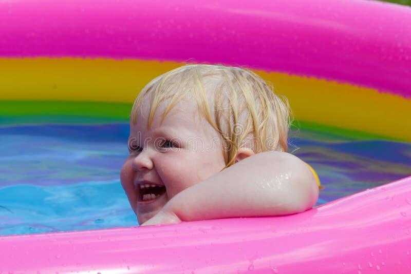 Маленькая счастливая девушка купает в раздувном бассейне стоковые изображения rf